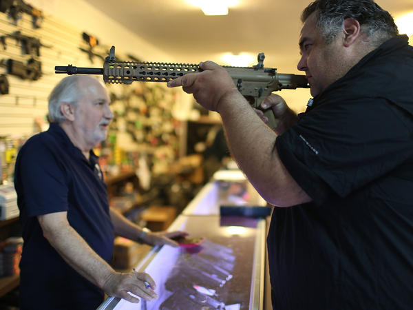 William Gordon, left, helps Steve Wrona as he looks at guns while visiting the K&W Gunworks store in Delray Beach, Fla., on Tuesday, the day President Obama announced executive action on guns.