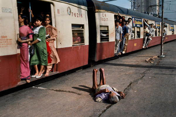A man lies on a train platform. Mumbai, 1994