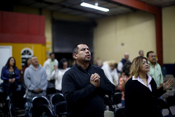 "Pastor Robert Salazar (center) prays before giving his sermon at the ""Cruising for Jesus"" mission of Tijuana. Salazar's church also runs a men's drug-rehab shelter nearby to help deported veterans."