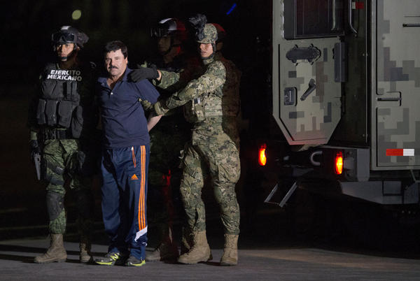 """Mexican drug lord Joaquin """"El Chapo"""" Guzman is escorted by army soldiers to a waiting helicopter, at a federal hangar in Mexico City Friday. The world's most wanted drug lord was recaptured six months after he fled through a tunnel from a maximum security prison in a made-for-Hollywood escape that deeply embarrassed the government and strained ties with the United States."""