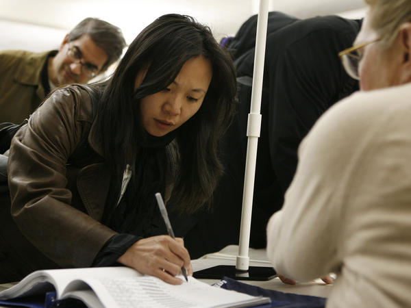Tanya Lau signs in to vote at the Chinese Community Church in Washington in 2010. Voter turnout has been low among Asian-Americans in recent elections, but a new superPAC hopes to increase it.