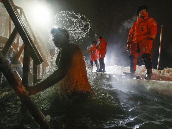 Rescue workers help Russian Orthodox believers marking Epiphany by swimming late Monday in a pond in Pushkin, outside St. Petersburg. Thousands of Russian Orthodox Church followers plunged into icy rivers and ponds across the country.