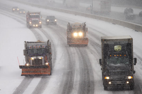 Snowplows and traffic make their way north along Interstate 95 as snow begins to fall in Ashland, Va., Friday. Portions of Virginia are under a blizzard warning.