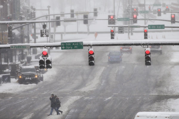 People cross a nearly empty Broadway, in the honky-tonk and entertainment district of Nashville, Tenn., on Friday. A blizzard menacing the Eastern United States started dumping snow in Virginia, Tennessee and other parts of the South on Friday as millions of people in the storm's path prepared for icy roads, possible power outages and other treacherous conditions.