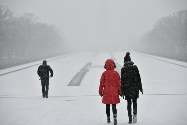 Visitors walk under snowfall in front of the Lincoln Memorial on Friday in Washington, D.C.