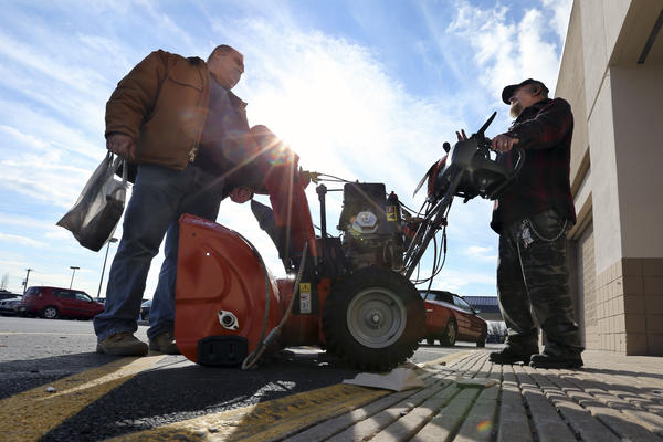 Two men discuss the pros and cons of various snowblowers outside a Lowe's home improvement warehouse Thursday in Langhorne, Pa. The northern Mid-Atlantic region, including Baltimore, Washington and Philadelphia, is preparing for a weekend snowstorm that is expected to reach blizzard conditions