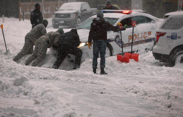 """National Guard members and other people help to push a police car that got stuck in the snow on January 23 in Washington, D.C. Heavy snow continued to fall in the Mid-Atlantic region causing """"life-threatening blizzard conditions"""" and affecting millions of people."""