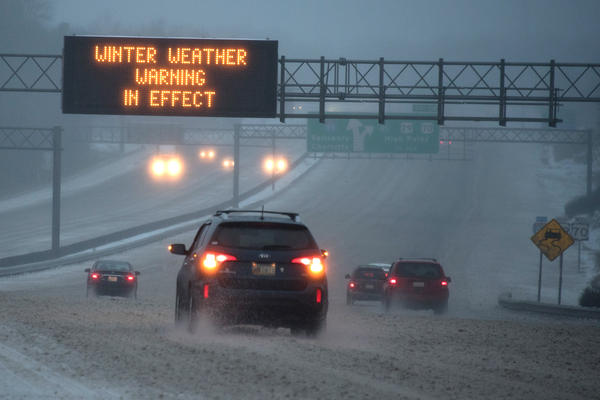 Vehicles move along Interstate 85 as an overhead sign indicates during a winter storm on Jan. 22 in Greensboro, N.C. A major snowstorm is forecasted for the East Coast this weekend with some areas getting up to 30 inches of snow.