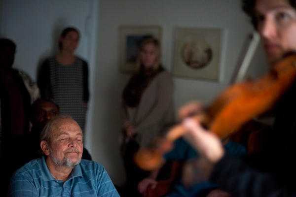 Wall listens to violinist Fain perform during the Make Room concert at Wall's apartment in Annapolis, Md. The concert is a fundraiser to help Wall pay his rent and shine a light on the growing lack of affordable housing.