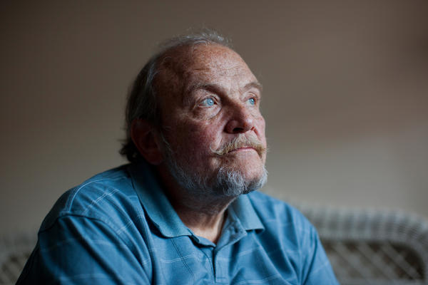Tom Wall sits in his bedroom before the Make Room concert begins on Jan. 18. Around 20 people gathered in Wall's small apartment to attend the concert and to help him, and others like him, pay the rent.