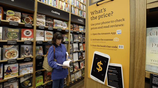 A customer looks at a book at Amazon Books, the first brick-and-mortar retail store for the online retail giant, on Nov. 3 in Seattle.