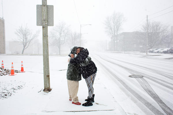 McDonald hugs Tyrone Knight, a previously homeless veteran, after spotting him walking along the road while she was out on a water run. She met Knight while trying to find him housing during her time working at My Brother's Keeper, a homeless shelter in Flint.