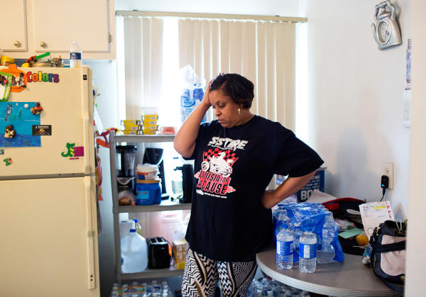 Jeneyah McDonald stands amid cases of bottled water in the kitchen of her home in Flint, Mich. Before water donations arrived in Flint, McDonald says, she spent an estimated $100 out of her $300 weekly grocery bill buying safe water for her family.