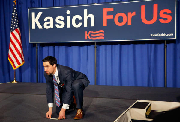 A campaign staffer places a stage marker as supporters of Ohio Gov. John Kasich wait for results in Concord. Kasich took second place in the Republican contest.