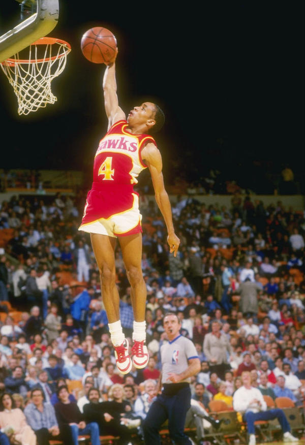 """Guard Anthony """"Spud"""" Webb of the Atlanta Hawks leaps to victory during a game against the Los Angeles Lakers at The Forum in Inglewood, California. (Stephen Dunn/Allsport via Getty Images)"""