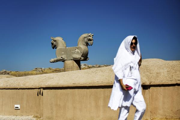 A foreign tourist at Persepolis walks past a statue of a double griffin, a mythical animal with the body of a lion and head and wings of an eagle.