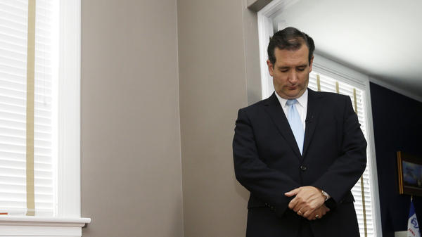 Ted Cruz, R-Texas, bows his head in prayer before speaking at a campaign event.