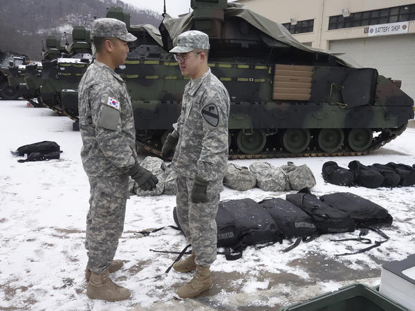 "An American soldier (right) from the First Armored ""Ironhorse"" Brigade of the 1st Calvary Division is among those who began arriving in South Korea in mid-January. They are replacing U.S. troops that cycle out in February. He's speaking with a South Korean soldier who's part of an integrated U.S.-South Korean division."