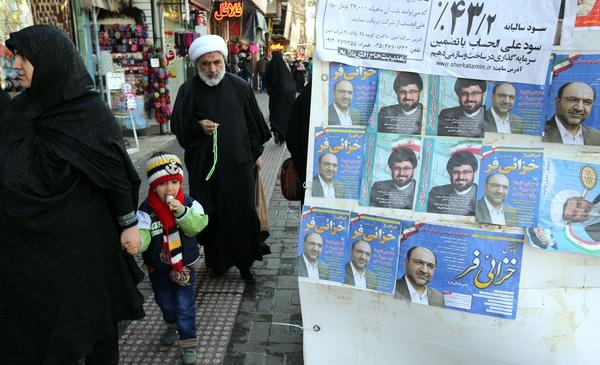 Iranians in Qom walk past electoral posters on Wednesday. Parliamentary elections are being held in Iran on Friday. Few people in Qom believe more engagement with the West is a good idea.
