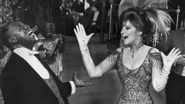 Louis Armstrong and Barbra Streisand have a laugh on the set of <em>Hello, Dolly!</em> The 1969 musical comedy won an Oscar for its score, co-composed by Lionel Newman.
