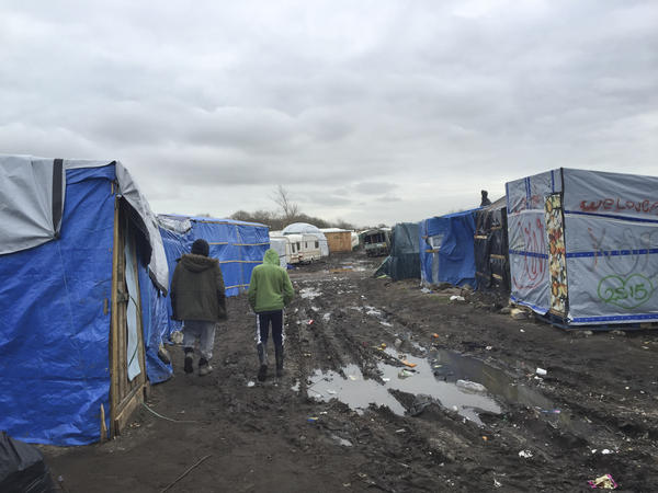 """Amran, an unaccompanied minor from Afghanistan, at right, walks in the camp known as the Jungle with 35-year-old Farid Hamdan, a father of four, also from Afghanistan. """"My heart is saying help him because he's only a kid,"""" says Hamdan. """"He has nobody else here to look after him."""" There are 300 to 400 children staying in the Jungle."""