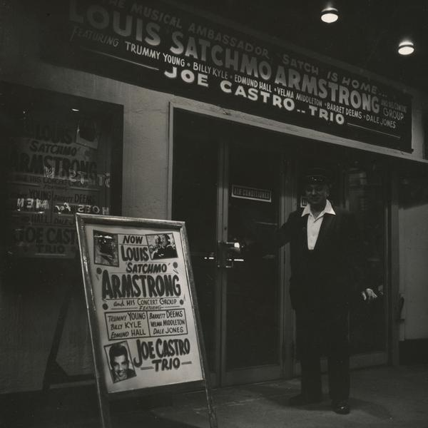 An usher stands with billboards advertising performances by Louis Armstrong and Joe Castro outside Basin Street in New York.