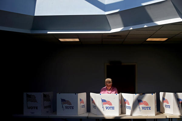 A voter casts her ballot at Fairfax Circle Baptist Church in Fairfax, Va.