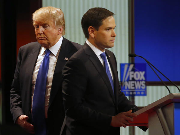 Donald Trump passes behind Marco Rubio during a commercial break in Thursday's Republican presidential primary debate at Fox Theatre in Detroit. All of the candidates Thursday said they would stand behind Trump if he is the eventual GOP nominee.