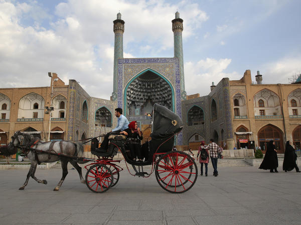 People ride a horse and carriage at sunset in Isfahan's UNESCO-listed central square on June 2, 2014 in Isfahan, Iran. Isfahan, with its immense mosques, picturesque bridges and ancient bazaar, is a virtual living museum of Iranian traditional culture, and is Iran's top tourist destination.