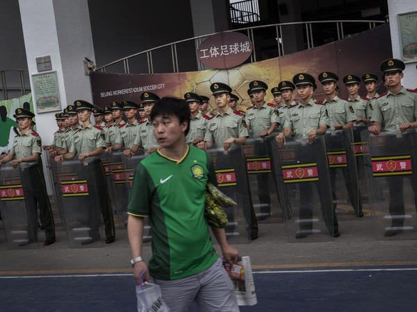 A Beijing Guoan supporter passes police officers before a match in 2015. The Chinese government hopes to transform China into a soccer power by mandating soccer programs in schools and investing in the Super League.
