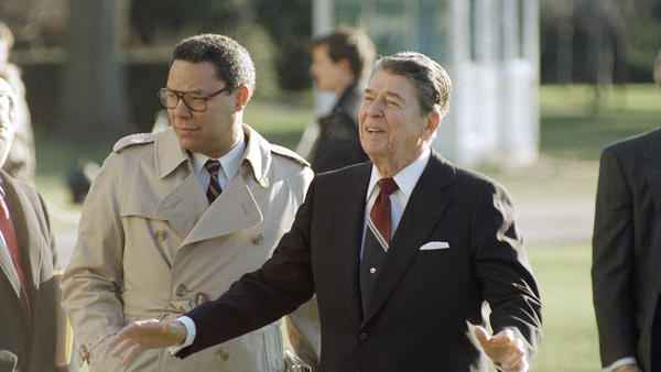 Colin Powell, during his time as national security adviser, accompanies President Reagan as he leaves the White House on Dec. 16, 1988.