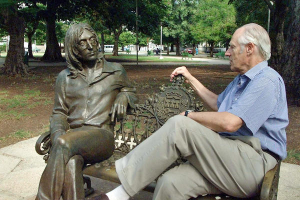 Martin shares a seat with a statue of John Lennon in a park of Havana, Cuba, in 2002. Martin visited Cuba to offer conferences on the Beatles and to participate in concerts with Cuban musicians.
