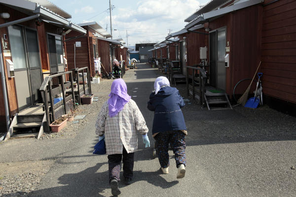 Elderly women walk together down a road lined with temporary homes in Fukushima prefecture, two hours from the radiation-affected coast.