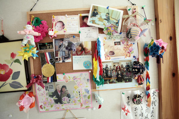 Pictures and letters decorate a wall of Saki Sato's temporary home.