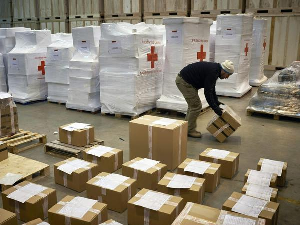 Employees prepare a convoy of four trucks transporting warm clothes and shoes to refugees in Ukraine, at the initiative of the French Red Cross, on Feb. 26 in Saint-Quentin-Fallavier, France.
