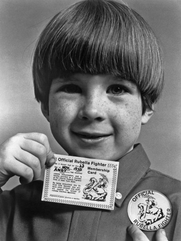 "A little boy shows off the ""Official Rubella Fighter"" membership card and button he received after being immunized against the German measles. This public health campaign against the virus ran through the early 1970s."