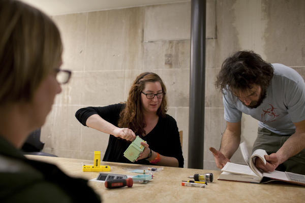 Matt McEntee (right) helps Esti Brennan (middle) fix her Polly Pocket clock while Susanne Unger (left) observes the process.