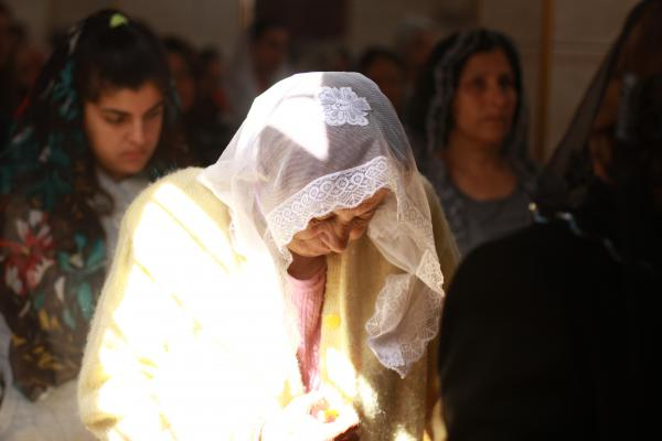 An Assyrian Christian woman prays at a church service in Tell Tamer, Syria. The service is to remember members of the community killed after about 300 people were taken captive by ISIS in March 2015.