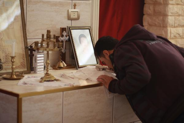 An Assyrian Christian man kisses a cross after taking communion in Tell Tamer, Syria. A photograph shows one of at least three people killed after ISIS took about 300 people captive in March 2015.