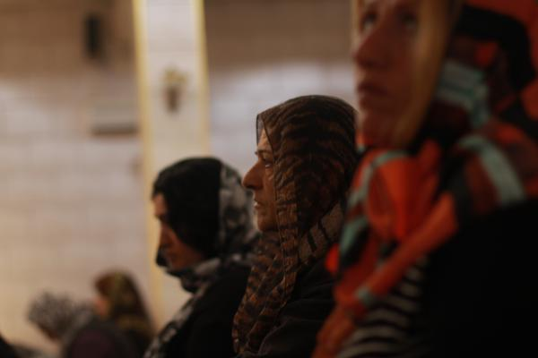 Women at a service in the Church of Our Lady in northern Syria. The women sit at the back, and cover their heads with scarves — a selection of colorful headscarves are kept at the back of the church.