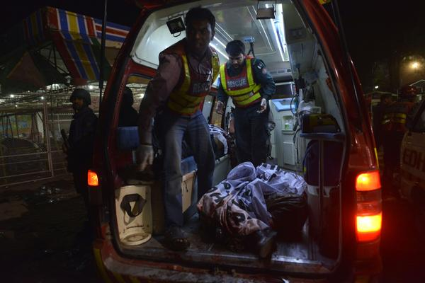 Rescuers carry a body in an ambulance from the bomb blast site.