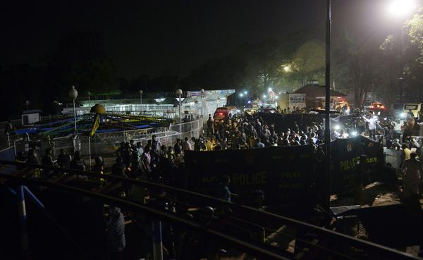Officials and rescuers gather at the blast site, next to an amusement ride.