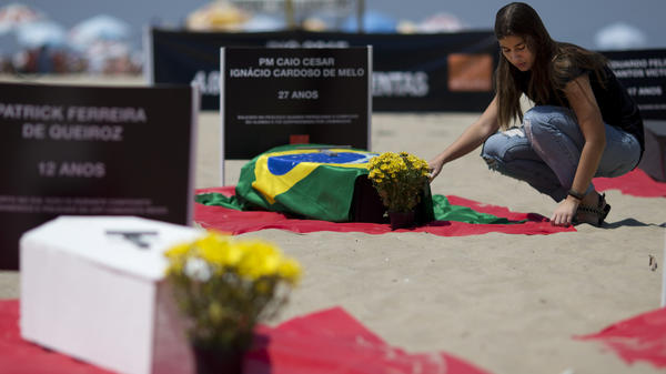 A woman places flowers on a coffin during a protest against violence in Rio de Janeiro last October. Brazil's violence is at an all-time high, with nearly 60,000 murders a year.