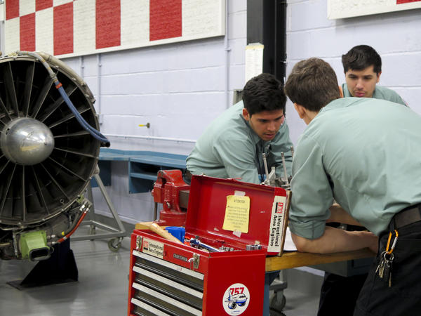 Students work on a reciprocating engine, used for small aircraft.