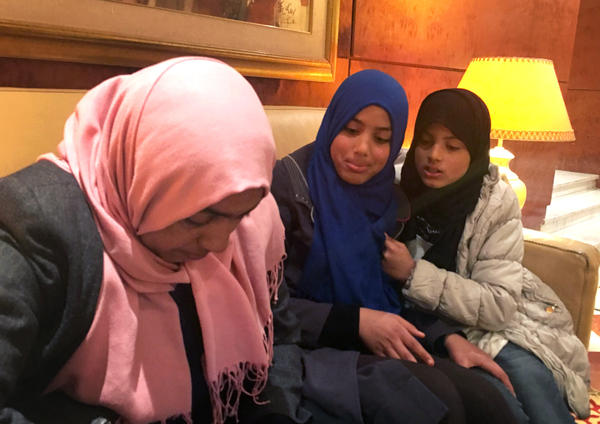 Taysir Sheikhawi, 11 (right), and her sister Aya, 13, look on as their mother, Olfa Hamrouni, pulls out pictures of their two older sisters, who joined ISIS.