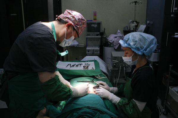 Dr. Hong Jung Geun, chief surgeon at Metro Plastic Surgery Clinic in Seoul (left), performs a pro-bono scar removal procedure on a former North Korean.