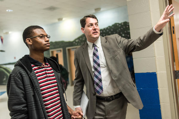Principal Charles Gregory (right) asks Robert Gordon to watch students in the middle school hallway during class change.