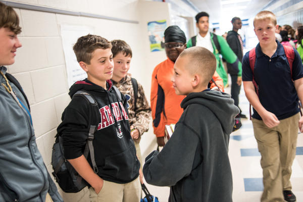 North middle school student and protege of Robert Gordon, Casey Robinson (second from left) chats with classmates in the hallway. Gordon has been preparing Robinson to take over his role after graduation.