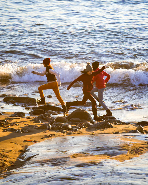 Schoolkids play in the fading light and surf along a small Nuuk beachfront.