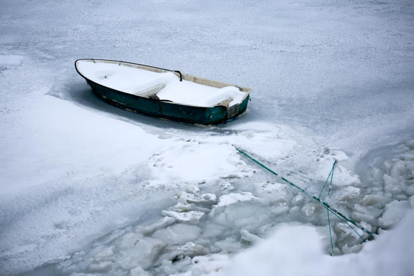 A lone rowboat sits icebound in a Nuuk harbor.
